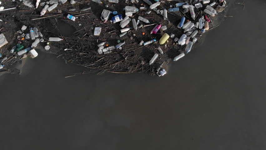 Spain - October 28, 2018: Aerial drone video waterfront scrap-heap garbage pile. Above view plastic bottles rubbish pollution marine debris on lake shore. Global damage environmental dumping concept