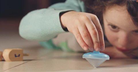 Close up shot of a girl spinning a Hanukka dreidel on the floor