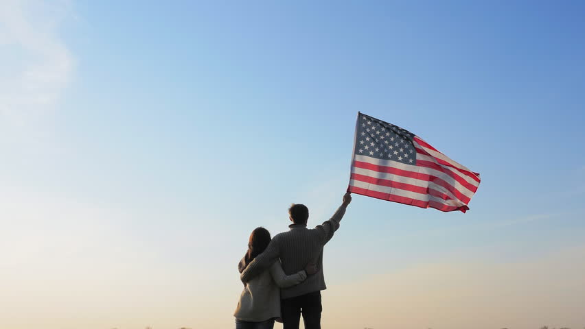 A man and a woman are embracing holding large flag of America in their hands against a blue sky. Patriotism, independence #1018895746