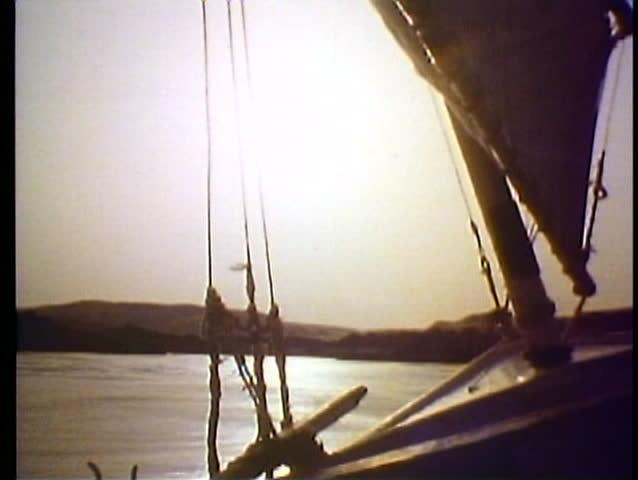 ASWAN, EGYPT, 1977, Sunset on the Nile, a feluca, sailboat glides down the Nile
