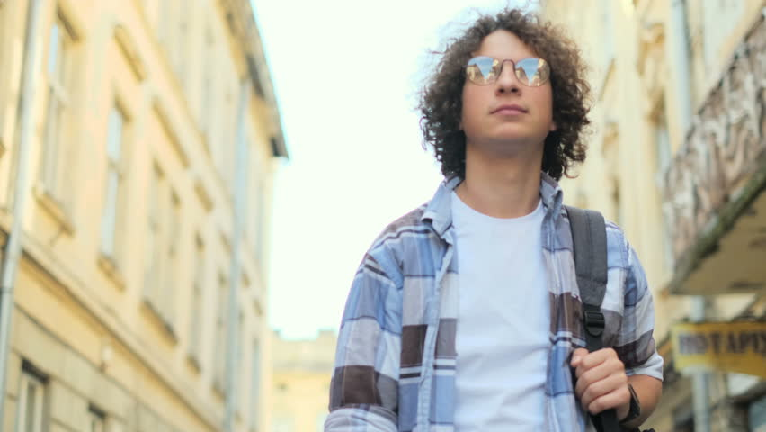 Portrait shot of smiling and laughing handsome curly young man wearing eyeglasses walking on street of old town center in europe at sunlight, looking at camera. Student, urban concept.