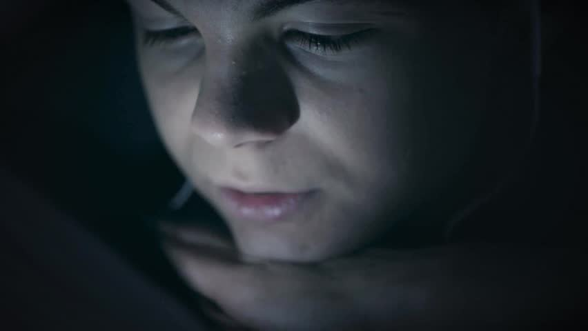 Boy watching movie or playing games on tablet computer at night. Child with headphones under blanket on bed using smartphone or tablet pc. Caucasian boy to make video call to talk to friends.  | Shutterstock HD Video #1018965016