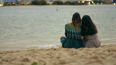 Two young women joined by their boyfriends who cuddle them on the beach, looking at the horizon at sunset. Wide shot from behind on 4K RED camera with shallow depth of field.