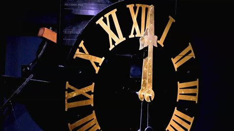 The clock with gilded Roman numerals shows exactly twelve hours. A bells on clock tower beat accurately the midnight. Clock mechanism with the bells.