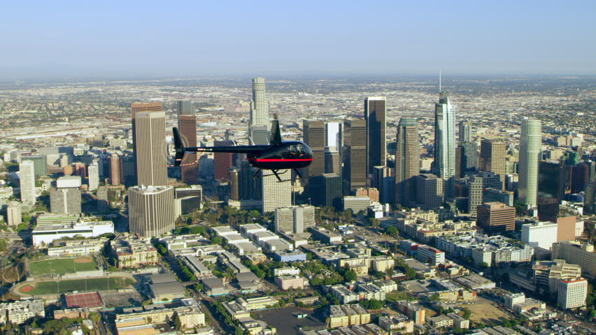 Aerial view of helicopter flying over city with downtown in background during the day in Los Angeles, California. Shot on 4K RED camera.