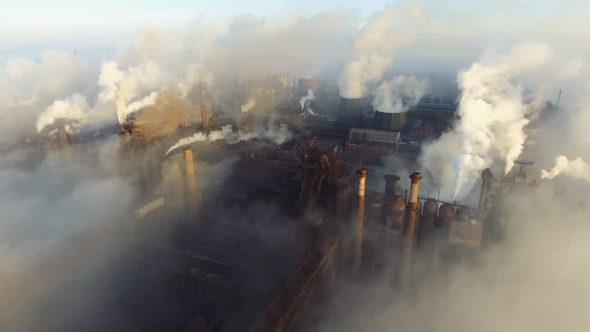 Aerial view. Pipes Throwing Smoke in the Sky. Large Plant on the Background of the City.