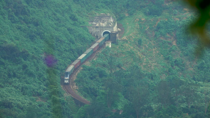 AERIAL: Long freight train comes out of the tunnel and moves through the lush exotic forest covering the remote island. Train crossing the breathtaking Hai Van Pass. Spectacular green mountains. | Shutterstock HD Video #1019108716