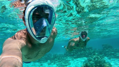 Underwater selfie - Adult couple snorkeling and seeing beautiful corals in Bora Bora