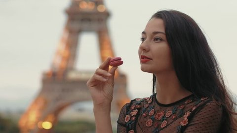 Paris woman smiling eating the french pastry macaron in Paris. Evening Eiffel tower with lights in the background. Portrait of gorgeous romantic young sensual girl in fashion black sexy dress enjoying