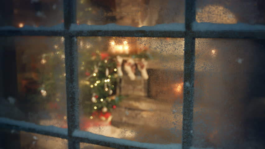 Christmas tree scene through frozen window. Traditional scene with presents under the tree and fire in fireplace. Decorated living room and candle light and socks with presents on fireplace sims. | Shutterstock HD Video #1019152486