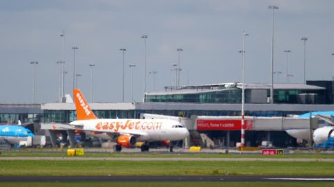 AMSTERDAM, THE NETHERLANDS - JULY 25, 2017: EasyJet Airbus A319 G-EZAC taxiing after landing, Shiphol Airport, Amsterdam, Holland