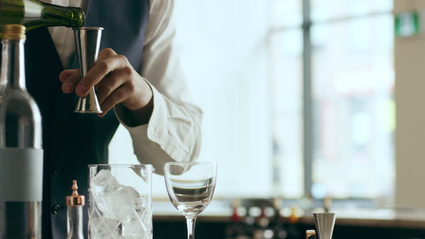 Bartender mixologist combining ingredients and making a Martini cocktail in a beautiful modern trendy bar. Close up on a RED camera. | Shutterstock HD Video #1019202766