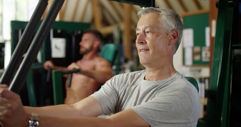 4K Funny gym concept - unfit mature man envious of muscly man working out with weights