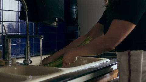 Cook washing celery in a large kitchen with an array of a equipment and appliances in the background. Medium close on a RED camera.
