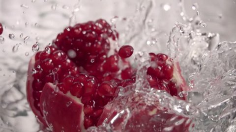 Falling splitted pomegranate into the water . Slow motion