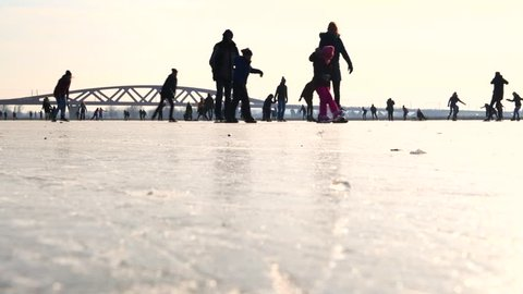 ZWOLLE, THE NETHERLANDS - MARCH 2: People ice skating on a frozen lake next to the river IJssel in Holland during a beautiful winter day winter. People are enjoying this typical Dutch winter activity.