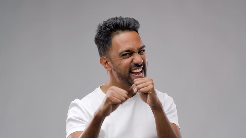 Competition, aggression and people concept - young indian man pretending fighting or boxing over grey background | Shutterstock HD Video #1019318866