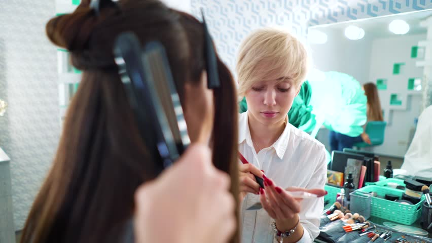 Woman with long dark hair getting professional makeup and hairstyle at beauty salon. Attractive girl sitting in front of mirror, talking to artist. people, cosmetics, hairstyle, lifestyle concept