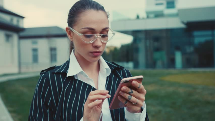 Camera moves around young businesswoman with glasses stand on street near business center and using modern smartphone smile lady elegant outside mobile cellphone close up   Shutterstock HD Video #1019385706
