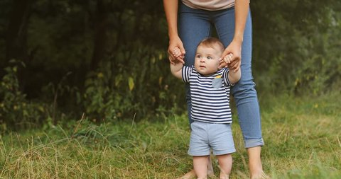 Portrait shot of the cute toddler boy walking barefeet with holding his mom's hands while learning stepping for the first time. Close up. Outdoors.