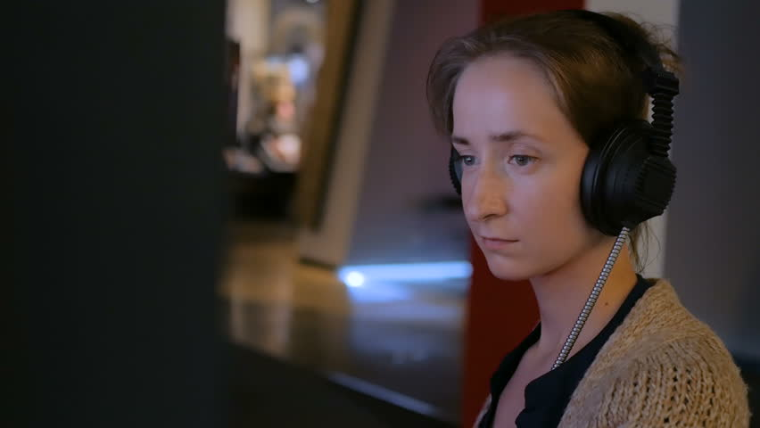 Woman touching interactive display, using headphones and listening audio guide at modern jewish history museum. Education and technology concept