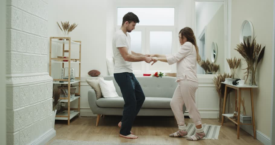 Sweet coup at home dacing in the living , home wearing clothes , cozy atmosphere. | Shutterstock HD Video #1019440306