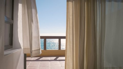 Balcony of a tropical luxury hotel by the ocean in 4k. Inside looking out at white curtains blowing in a warm summer wind with the ocean stretching out in the background. Wide shot depicts wanderlust.