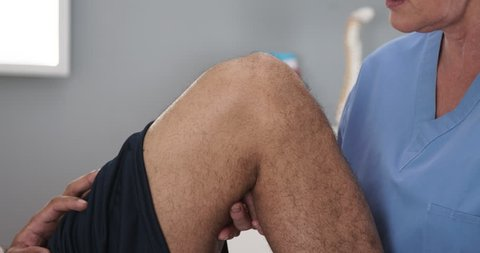 Close up of senior doctor examining male patients injured knee. Tight shot of african-american mans leg bending with assistance of professional MD or physical therapist