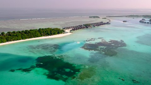 4K Top View of the Tropical Lagoon Sea Surface. Luxury 5 Star Resort Hotel. Water Bungalow hut Relaxing Holiday. Aerial Video of a Small Tropical Island in Maldives Island. Palm Tree on the Sandbank