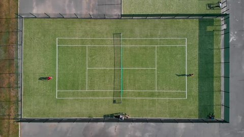 Shooting from the drone over the tennis court where people play in the tennis