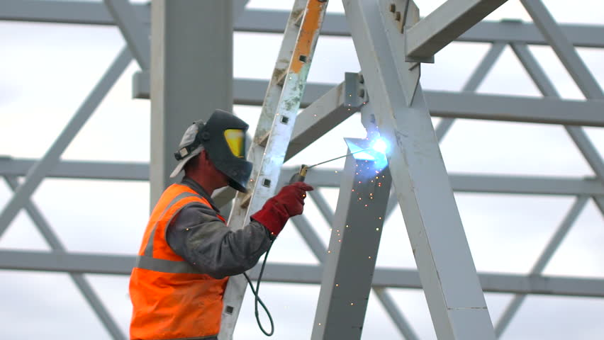 Industrial worker welding of metal structures, welder man male worker soldering steel beam structure on new building on construction site. welder working. Sparks fly as one welder welds steel. builder