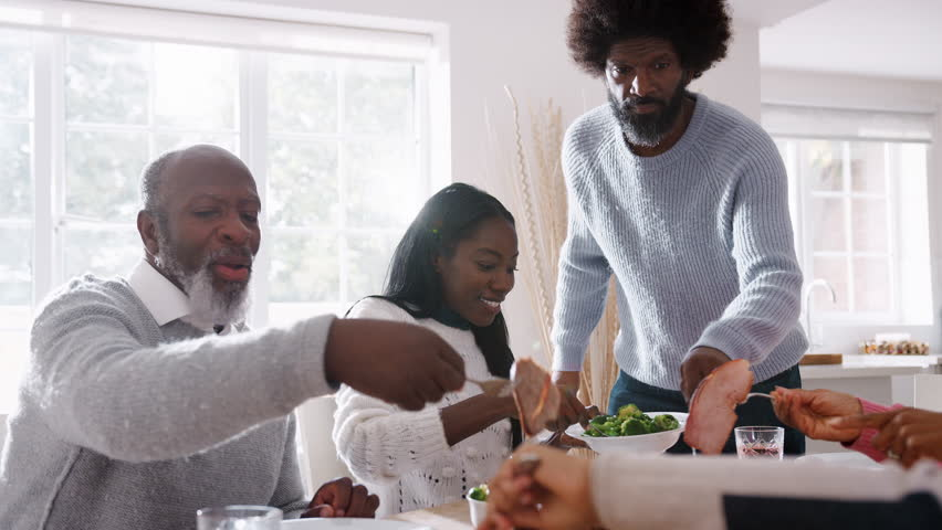 Multi generation mixed race family sitting at the table serving each other Sunday dinner at home, close up, backlit | Shutterstock HD Video #1019528146