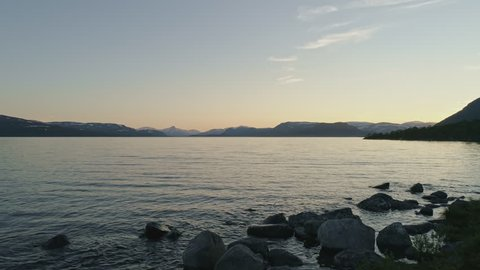 Peaceful summer night at lake Kilpisjärvi, Lapland, Finland. Mountains on the background camera tracking forward on the surface of lake. Great intro scene.