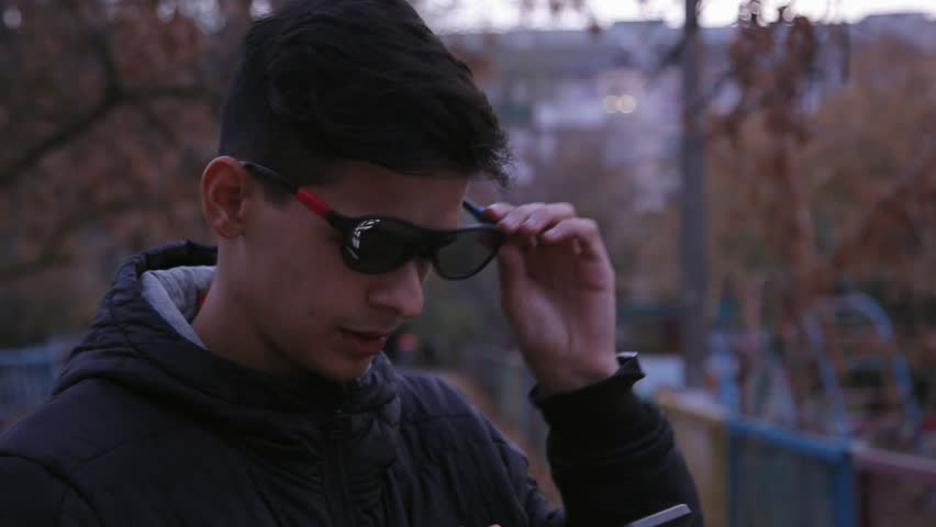 funny positive young boy in 3D glasses using smartphone outdoors, close up #1019585596