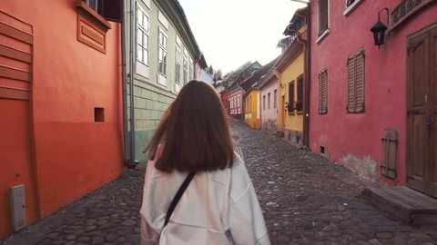 The girl walks on the street of the old city.