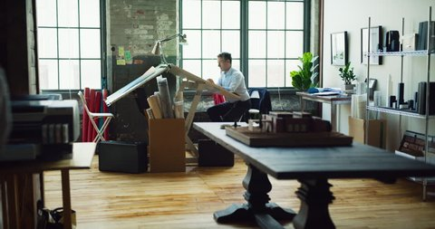 Architect man sits at drafting table in modern industrial office during the day. Wide to long shot on 4K RED camera.
