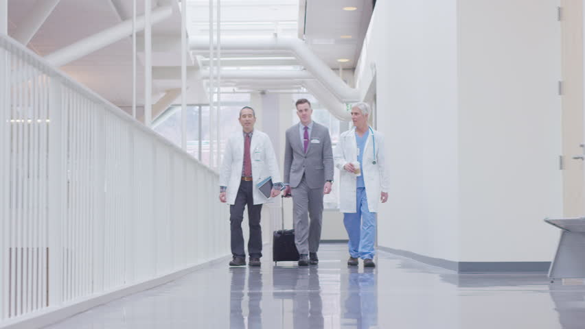 Handheld full length of male doctors discussing while walking in hospital corridor | Shutterstock HD Video #1019671786