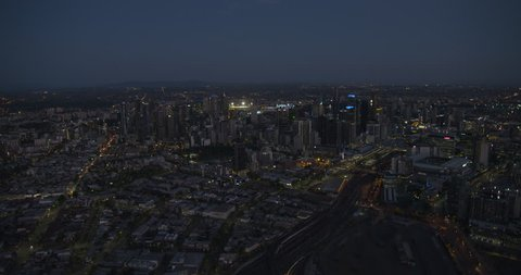 Aerial sunset view evening city lights Melbourne CBD with railway tracks passing Marvel Stadium Dockland Victoria Australia