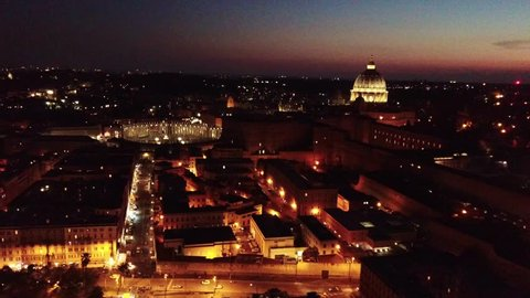 Aerial drone night video of Saint Peter's square, world's largest church - Papal Basilica of St. Peter's, Vatican - an elliptical esplanade created in the mid seventeenth century, Rome, Italy