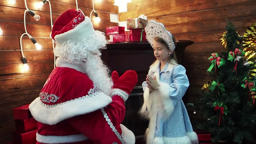 Father Frost Santa Claus and the little girl Snegurochka play palms. New Year's Christmas fairy tale characters of the Russian tradition play pat-a-cake at a fireplace and a fir-tree.