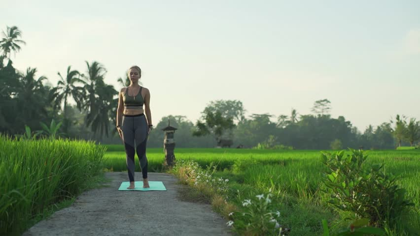 Fit girl do yoga extended hand to big toe pose at rice field rapid slow motion