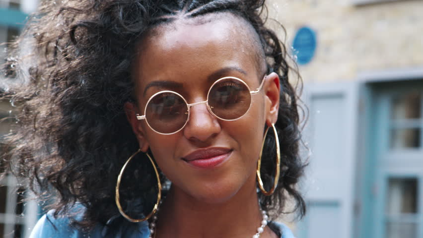 Trendy young black woman wearing round sunglasses turning to look back to the camera, head and shoulders, close up