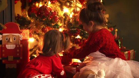 Children play in the Christmas atmosphere, laugh and enjoy gifts. Babies are sitting on the floor near the warm fireplace and the New Year tree. Sisters open the box and decorating the Christmas tree.