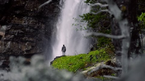 Man standing in front of a huge waterfall, enjoying nature on it's finest. Norway, Europe at day time