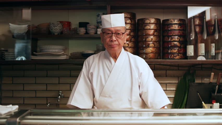 Portrait of Accomplished Japanese sushi chef standing behind a counter in his small traditional sushi bar with soft interior lighting. Medium shot on 4k RED camera. | Shutterstock HD Video #1019910586