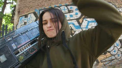 Cool stunning brunette with retro boombox looking into camera enjoying music, dancing. Portrait of cheerful girl in background of street art. Graffiti on wall. Outdoors.