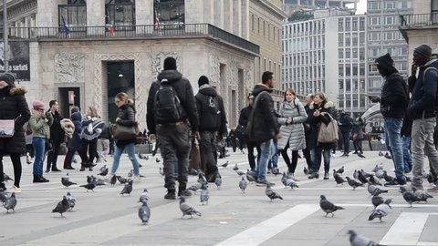 """Milan, Italy - Nov 22, 2018: African immigrants selling / scamming money from tourists for """"friendship bracelets"""" at Piazza Duomo in Milan, Italy - a common scam to avoid while visiting Milan"""