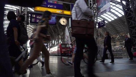Commuters walk fast, people hurry run to train in Frankfurt Main Railway Station. Passengers go in rush inside Deutsche Bahn Central Building, Frankfurt Hauptbahnhof interior, Germany, April 20, 2018