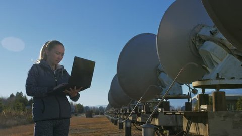 Woman student operator of institute of Solar Terrestrial Physics monitors communication equipment in notebook. Unique array solar radio telescope.