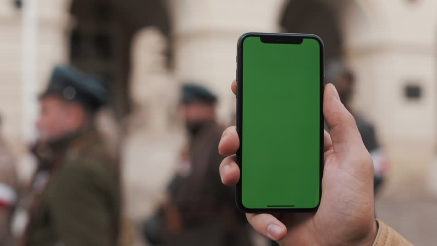 Closeup of a man's hand holding and using mobile telephone with a vertical green screen on the streets. Military soldiers in the background | Shutterstock HD Video #1020111586